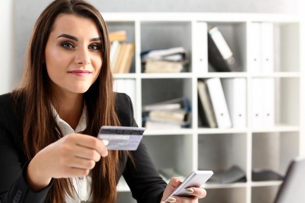 La donna di affari nell'ufficio tiene un credito di plastica
