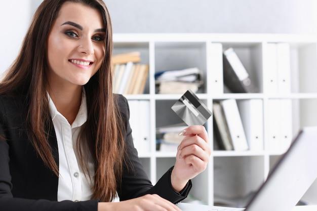 La donna di affari nell'ufficio tiene una carta di debito di plastica di plastica in sua mano