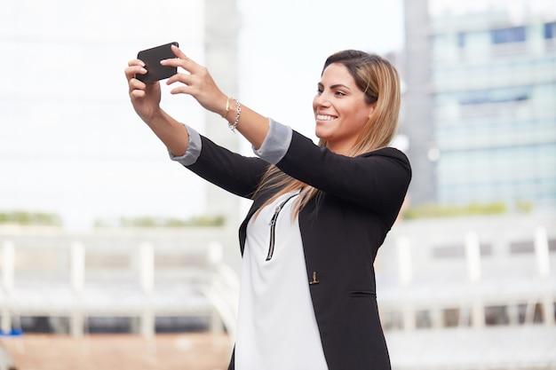 La donna di affari prende un selfie nell'ambiente urbano