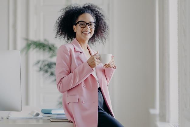 La donna di affari rilassata tiene la tazza della bevanda calda, ha la pausa caffè, sta vicino al suo posto di lavoro in spazioso armadio bianco indossa occhiali lunghi giacca rosa funziona in ufficio. tempo di riposo dopo il lavoro