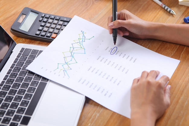 La donna di affari scrive il punto culminante del cerchio sulla relazione di attività con il computer portatile e il calcolatore su fondo di legno