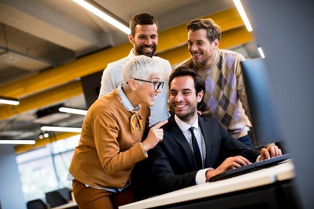 La donna di affari senior e i giovani uomini d'affari lavorano in un ufficio