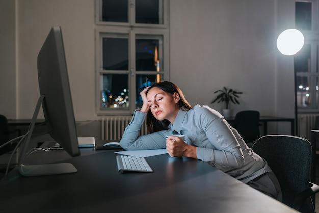 La donna di affari si è addormentata alla scrivania. lavoro straordinario.