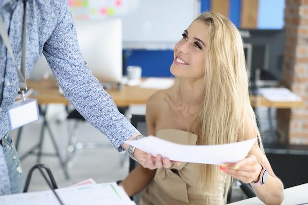 La donna di affari sorride al suo collega e frusta il suo documento