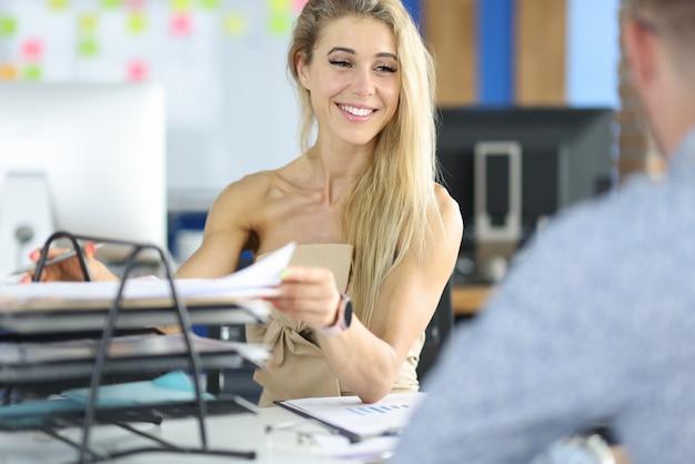 La donna di affari sorride al suo collega ed estrae i documenti dal vassoio.