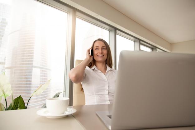 La donna di affari sorridente risponde alla chiamata in ufficio
