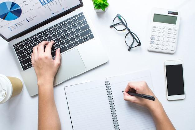 La donna di affari sta prendendo le note e sta usando i calcolatori ed i computer portatili su una tavola bianca. vista dall'alto.