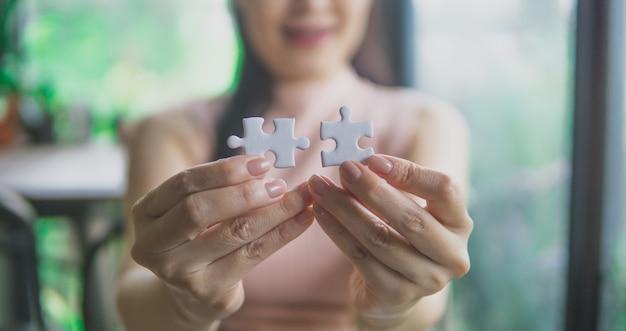 La donna di affari sta provando a collegare il pezzo di puzzle delle coppie.
