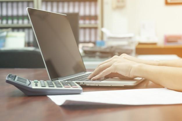 La donna di affari sta scrivendo e usa il calcolatore e la carta sulla tavola