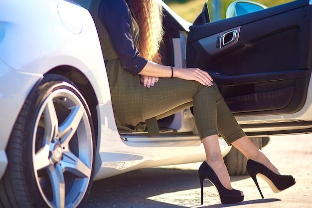 La donna di affari sta sedendosi in un'automobile costosa. gambe con scarpe a tacco alto.