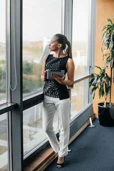 La donna di affari sta stando nell'ufficio vicino alla finestra e sta studiando i documenti. affari, finanza, avvocato