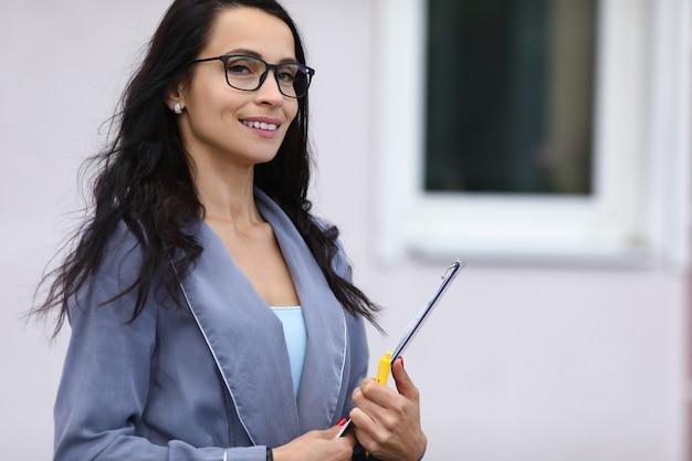 La donna di affari sta sulla via e tiene la lavagna per appunti in sue mani