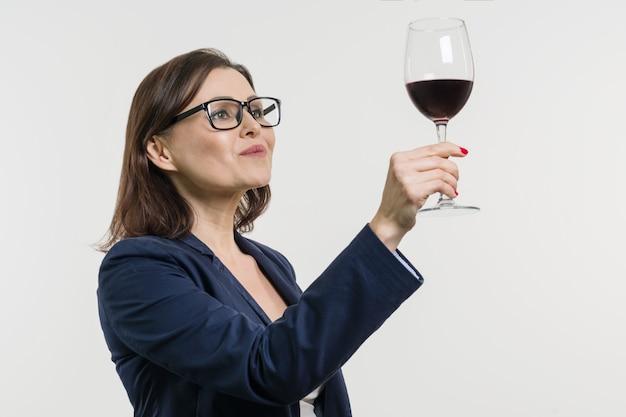 La donna di affari sta tenendo e guardando un bicchiere di vino rosso.