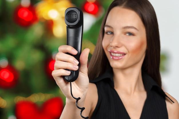 La donna di affari sta tenendo il microtelefono del telefono it