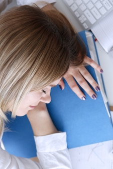La donna di affari stanca ad area di lavoro in ufficio prende il pisolino