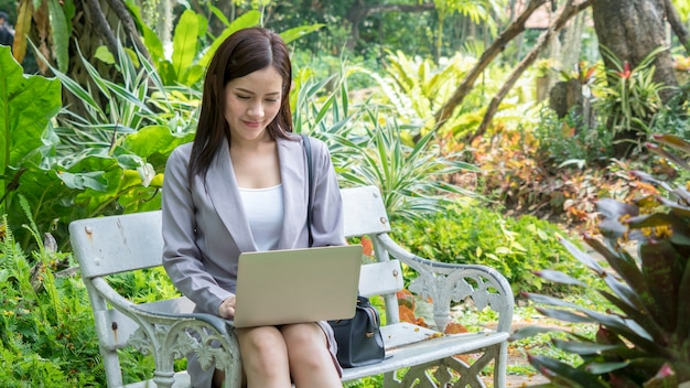 La donna di affari usa il computer e pensa nel parco giardino