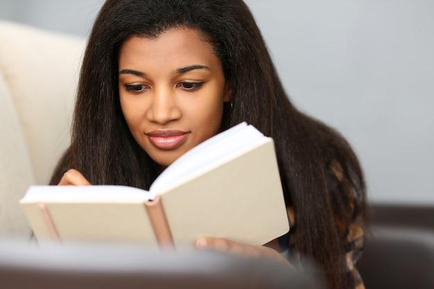 La donna di colore sorridente scrive la storia in taccuino
