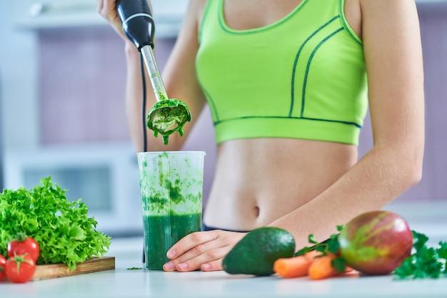 La donna di dieta in abiti sportivi prepara un frullato verde usando un frullatore a immersione in cucina.