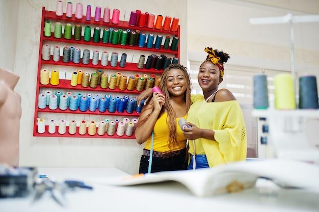 La donna di due sarti da donna africana cuce i vestiti sulla macchina per cucire e seleziona i fili all'ufficio del sarto. ragazze da sarta nere.