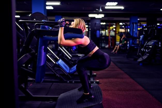 La donna di forma fisica che fa gli affondi si esercita per l'allenamento di allenamento del muscolo della gamba in palestra