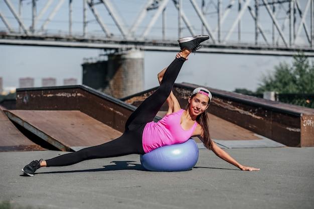 La donna di forma fisica che fa l'allungamento si esercita con la palla di misura sul fondo urbano della città