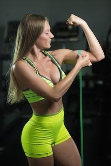 La donna di forma fisica con la misura di nastro misura la circonferenza del bicipite