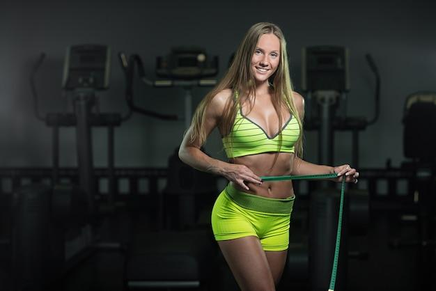La donna di forma fisica con la roulette misura la circonferenza dell'addome