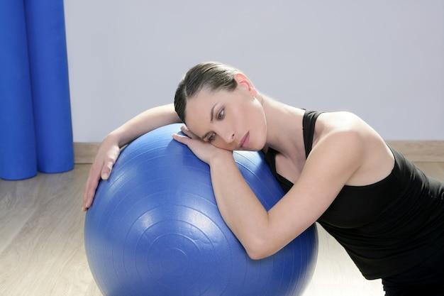 La donna di forma fisica di aerobica si rilassa il bal blu di stabilità dei pilates