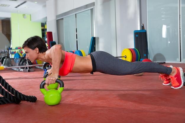 La donna di forma fisica di crossfit spinge l'esercizio di pushup di kettlebells