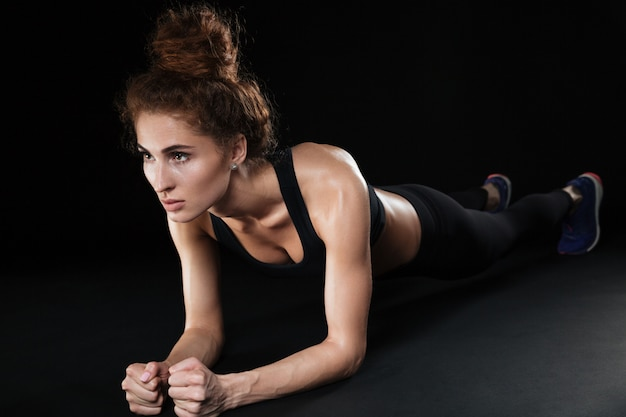 La donna di forma fisica fa l'esercizio della plancia