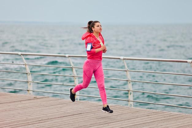La donna di forma fisica in abiti sportivi sta correndo sulla spiaggia. corsa mattutina.