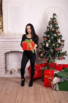 La donna di forma fisica nello stile di sport copre con il contenitore di regalo di natale in sue mani vicino all'albero di natale