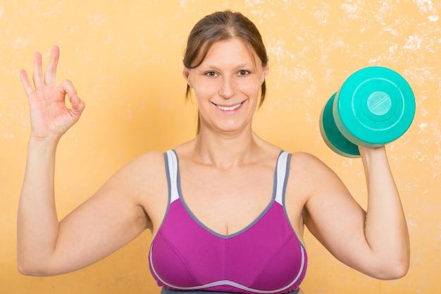 La donna di forma fisica sta facendo i pesi per le braccia a casa