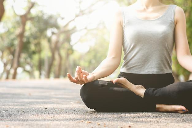 La donna di forma fisica sta meditando sulle vie nel parco.