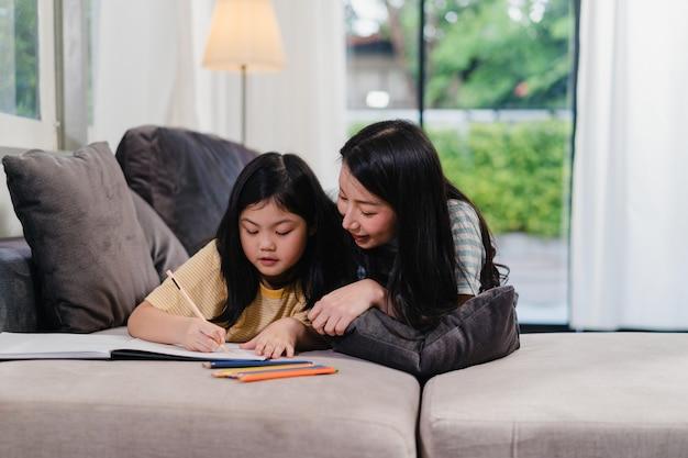 La donna di mezza età asiatica insegna a sua figlia a fare i compiti e disegnare a casa. stile di vita madre e bambino divertimento felice trascorrere del tempo insieme nel salotto di casa moderna la sera.