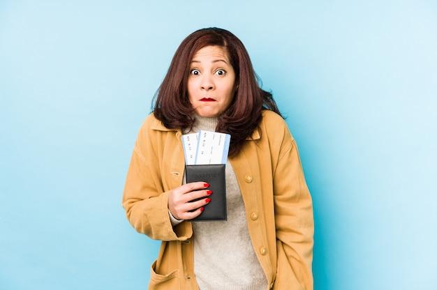 La donna di mezza età che tiene un passaporto scrolla le spalle le spalle e apre gli occhi confusi.