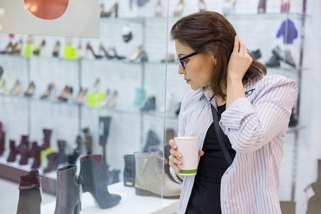 La donna di mezza età esamina la vetrina della scarpa