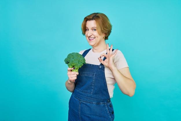La donna di mezza età sta per mangiare un broccolo