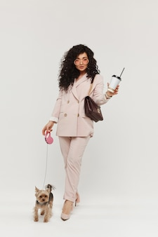 La donna di modello nella tenuta dell'attrezzatura alla moda porta via la tazza di caffè e cammina con il piccolo yorkie terrier