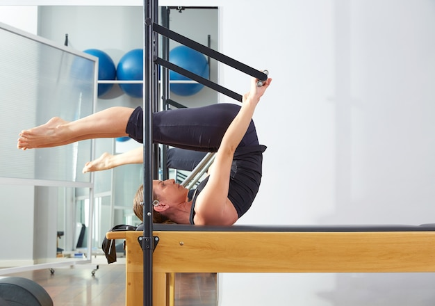 La donna di pilates in riformatore si rivoltò l'esercizio