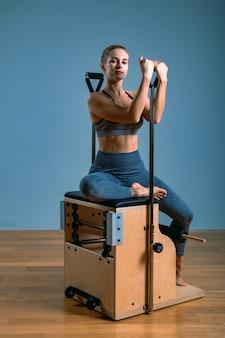 La donna di pilates in un riformatore che fa l'allungamento si esercita in palestra. concetto di fitness, attrezzature speciali per il fitness, stile di vita sano, plastica. copia spazio, banner sportivo per la pubblicità