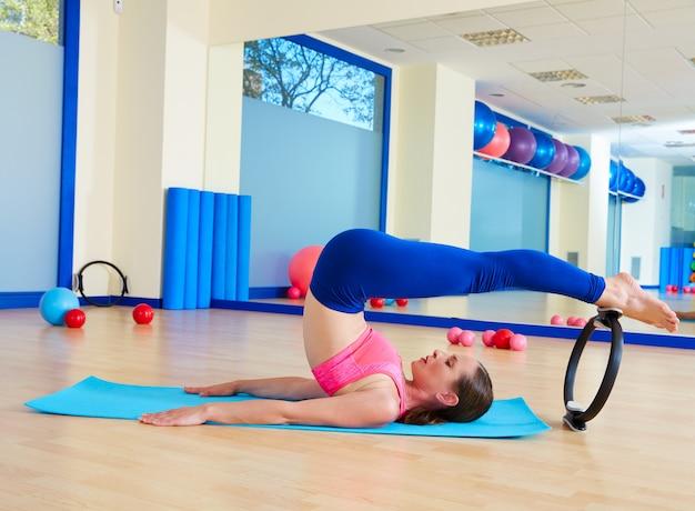La donna di pilates rotola sopra l'esercizio magico dell'anello