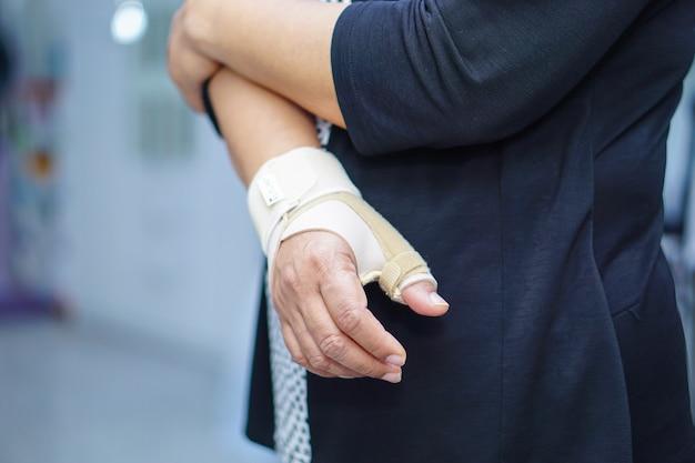 La donna di signora di mezza età asiatica usa la fasciatura elastica per trattare la sindrome di de quervain a portata di mano e il dito in ufficio.