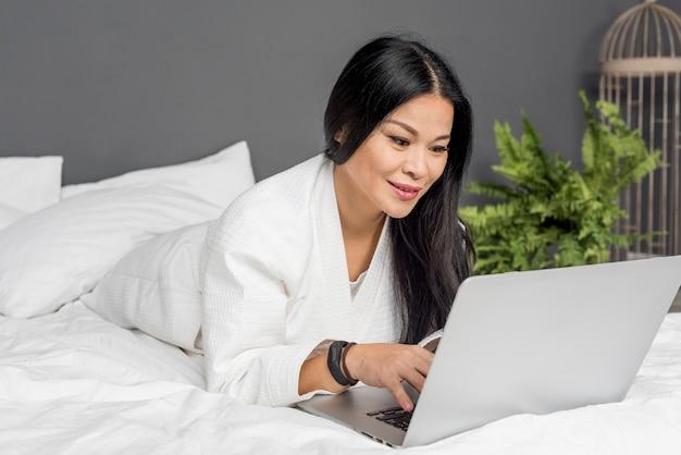 La donna di smiley risiede nel letto con il computer portatile