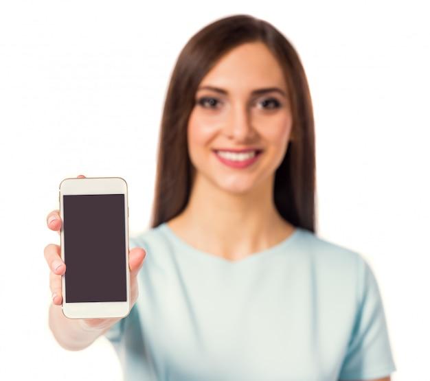La donna di sorriso sta utilizzando il telefono su bianco.