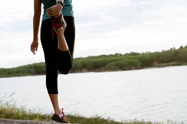 La donna di sport sta allungando il muscolo dopo l'allenamento
