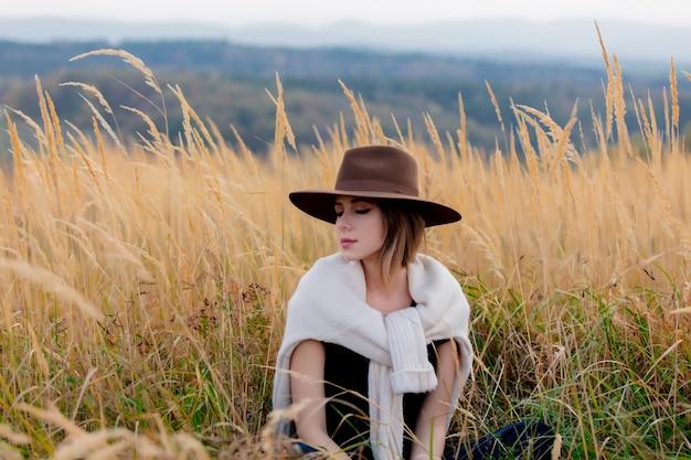 La donna di stile in maglione si siede in erba gialla alla campagna con le montagne