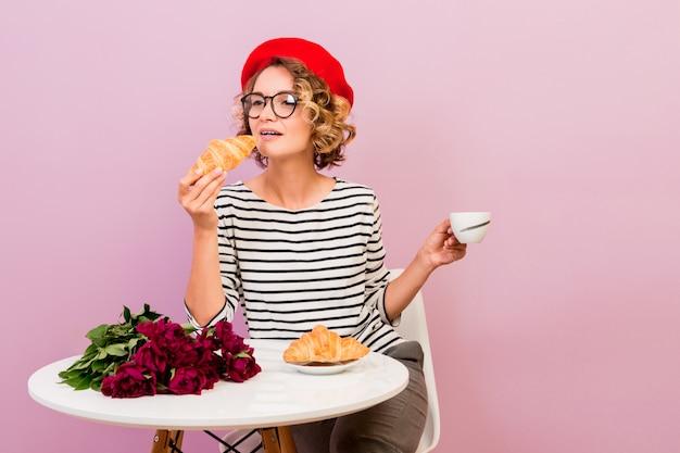 La donna di viaggio felice in francia che mangia i croissans con caffè, si siede dalla tavola sul rosa.