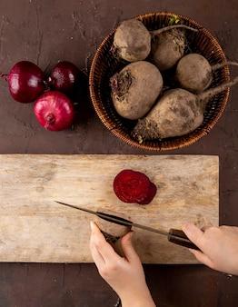 La donna di vista superiore taglia le barbabietole su una lavagna con le barbabietole fresche in un canestro con le cipolle rosse