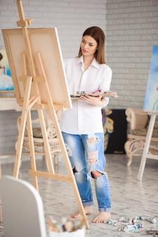 La donna dipinge l'immagine su tela con le pitture ad olio nel suo studio